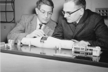 Model of the MP Tandem Van de Graaff particle accelerator installed at Chalk River is examined by G.C. Hanna and L.G. Elliot